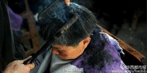 Begini cara Wang cukur rambut dengan besi panas.(Odditycentral)